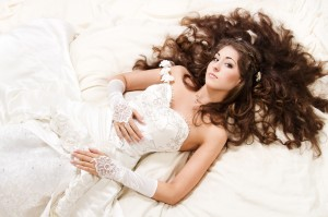 Bride with curly long hair lying over white. High angle view. Fa